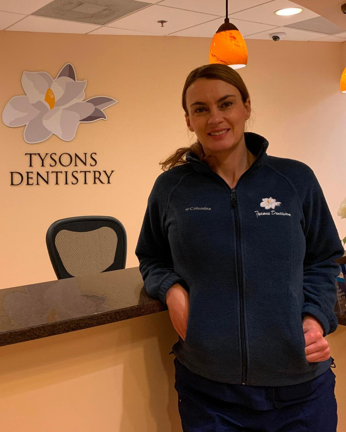 masha, our dental hygienist stands and smiles in our front office | dentist vienna va